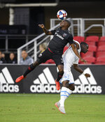 FILE - In this July 24, 2019, file photo, D.C. United defender Chris Odoi-Atsem, left, heads the ball against Marseille midfielder Niels Nkounkou, right, during the first half of an international friendly soccer match in Washington. When the MLS Is Back tournament starts next week in Florida, the vast majority of the league's players will be taking part. For some, that includes balancing their own personal underlying health concerns with the opportunity to return to their profession. hat includes the likes of Columbus goalkeeper Matt Lampson and D.C. United's Chris Odoi-Atsem, who have both overcome cancer.(AP Photo/Nick Wass, File)