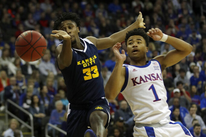 Kansas City guard Marvin Nesbitt Jr. (33) rebounds against Kansas guard Devon Dotson (1) during the first half of an NCAA college basketball game in Kansas City, Kan., Saturday, Dec. 14, 2019. (AP Photo/Orlin Wagner)