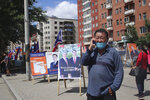 A man wearing a mask and using his phone stands near the election stand of Mongolian People's Revolutionary Party or MPRP featuring ex-president of Mongolia Enkhbayar Nambar and his son Batshugar in the Songinokhairkhan district on the outskirt of Ulaanbaatar, Mongolia, Monday, June 22, 2020. Mongolia holds parliamentary elections on Wednesday, continuing a nearly 30-year democratic system in a vast but lightly populated country sandwiched between authoritarian regimes in Russia and China and beset by economic problems. (AP Photo/Ganbat Namjilsangarav)