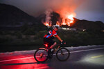 A cyclist rides along a trail as the Ranch Fire burns, Thursday, Aug. 13, 2020, in Azusa, Calif. Heat wave conditions were making difficult work for fire crews battling brush fires and wildfires across Southern California. (AP Photo/Marcio Jose Sanchez)