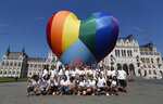 Activists pose for a photo after erecting a large rainbow-colored heart in front of the country's parliament building in Budapest, Hungary, on Thursday, July 8, 2021. The activists are protesting against the recently passed law they say discriminates and marginalizes LGBT people. (AP Photo/Laszlo Balogh)