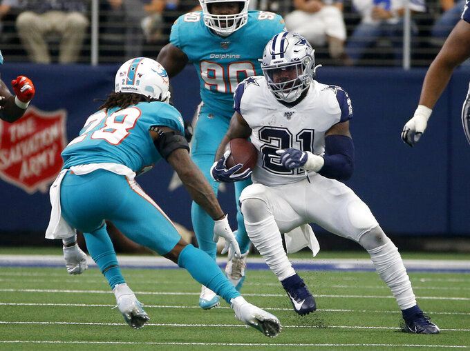 Miami Dolphins strong safety Bobby McCain (28) defends as Dallas Cowboys running back Ezekiel Elliott (21) carries the ball in the second half of an NFL football game in Arlington, Texas, Sunday, Sept. 22, 2019. (AP Photo/Ron Jenkins)
