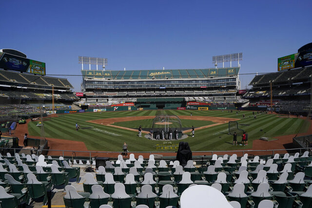 Cutouts are placed at Oakland Coliseum as Chicago White Sox players practice during a baseball workout in Oakland, Calif., Monday, Sept. 28, 2020. The White Sox are scheduled to play the Oakland Athletics in an American League wild-card playoff series starting Tuesday. (AP Photo/Jeff Chiu)