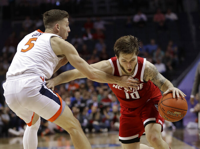 North Carolina State's Braxton Beverly (10) drives against Virginia's Kyle Guy (5) during the first half of an NCAA college basketball game in the Atlantic Coast Conference tournament in Charlotte, N.C., Thursday, March 14, 2019. (AP Photo/Nell Redmond)
