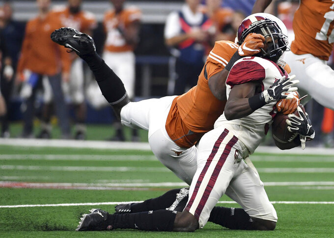 Texas defensive back Kris Boyd grabs the facemask of Oklahoma wide receiver Marquise Brown during the first half of the Big 12 Conference championship NCAA college football game on Saturday, Dec. 1, 2018, in Arlington, Texas. (AP Photo/Jeffrey McWhorter)