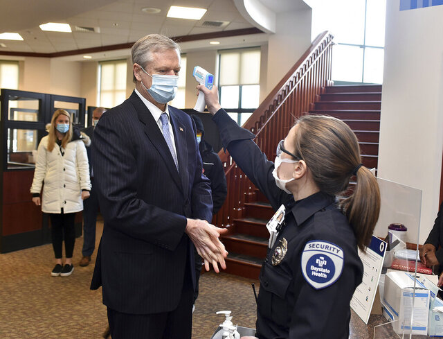 Massachusetts Governor Charlie Baker gets his temperature checked as he arrives at Baystate Medical Center to give an update on COVID-19 vaccinations Tuesday, Jan. 5, 2021, in Springfield, Mass. (Don Treeger/The Republican via AP)