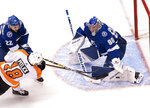 Philadelphia Flyers center Tyler Pitlick (18) gets hit by Tampa Bay Lightning defenseman Kevin Shattenkirk (22) as he shoots on goaltender Andrei Vasilevskiy (88) during the first period of an NHL hockey playoff game Saturday, Aug. 8, 2020, in Toronto. (Frank Gunn/The Canadian Press via AP)