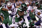 New York Jets' Le'Veon Bell (26) rushes past New England Patriots' John Simon during the first half of an NFL football game Monday, Oct. 21, 2019, in East Rutherford, N.J. (AP Photo/Adam Hunger)