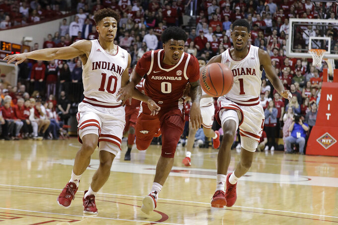Arkansas's Desi Sills (0) chases a loose ball against Indiana's Rob Phinisee (10) and Aljami Durham (1) during the first half in the second round of the NIT college basketball tournament, Saturday, March 23, 2019, in Bloomington, Ind. (AP Photo/Darron Cummings)