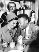 FILE - In this March 5, 1966 file photo, Brazilian soccer star Pele and his wife Rosemarie drink wine as Heuriger singers perform at a tavern in Vienna, Austria, one day after the couple arrived for thier honeymoon. On Oct. 23, 2020, the three-time World Cup winner Pelé turns 80 without a proper celebration amid the COVID-19 pandemic as he quarantines in his mansion in the beachfront city of Guarujá, where he has lived since the start of the pandemic. (AP Photo, File)