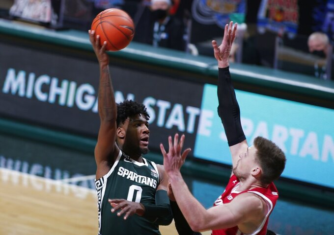 Michigan State's Aaron Henry, let, shoots against Wisconsin's Trevor Anderson during the first half of an NCAA college basketball game, Friday, Dec. 25, 2020, in East Lansing, Mich. (AP Photo/Al Goldis)