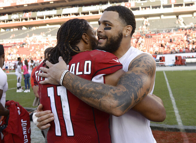 Arizona Cardinals wide receiver Larry Fitzgerald (11) hugs Tampa Bay Buccaneers wide receiver Mike Evans after an NFL football game Sunday, Nov. 10, 2019, in Tampa, Fla. (AP Photo/Jason Behnken)