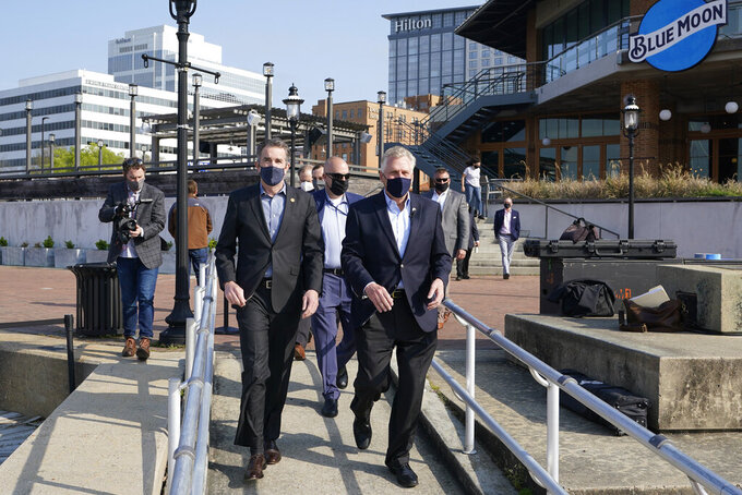Virginia Gov. Ralph Northam, left, arrives with former Gov. and Democratic gubernatorial candidate, Terry McAuliffe, right, for a news conference at Waterside in Norfolk, Va., Thursday, April 8, 2021. Northam endorsed McAuliffe for governor. (AP Photo/Steve Helber)