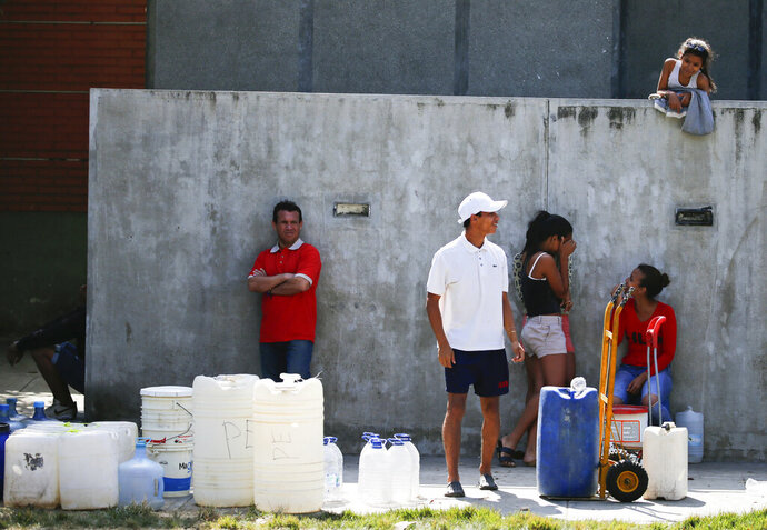 People wait in line to fill up containers with water from a public fountain in Caracas, Venezuela, Tuesday, March 12, 2019. Most people have been deprived of power, water and communications since last Thursday when nationwide power outages first hit, abruptly worsening conditions in a nation already struggling with hyperinflation and shortages of food and medicine. (AP Photo/Fernando Llano)