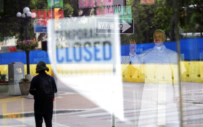 FILE - In this April 10, 2020, file photo, a pedestrian is reflected with a temporary closed sign in the window of a wax museum where a statue of Pope Francis is on display in San Antonio. For libertarians the very thought of massive government aid or the enforced closings of businesses is usually indefensible. But those beliefs can change in a time of crisis, like now. The spread of the coronavirus has renewed a long-running debate among libertarians over such core beliefs as private enterprise and individual autonomy. (AP Photo/Eric Gay, File)