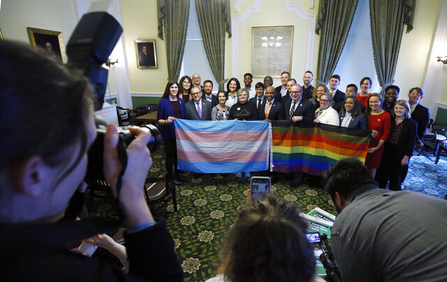 Supporters of SB 868 gather for a group photo after a press conference ahead of the floor votes on SB 868, the Virginia Values Act. The event was held in the Jefferson Room of the State Capitol in Richmond, Va., Thursday, Feb. 6, 2020. (Bob Brown/Richmond Times-Dispatch via AP)
