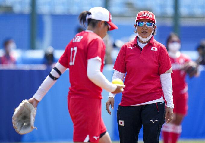 Japan head coach Reika Utsugi talks to player Yukiko Ueno during the softball game between Japan and Australia at the 2020 Summer Olympics, Wednesday, July 21, 2021, in Fukushima . (AP Photo/Jae C. Hong)