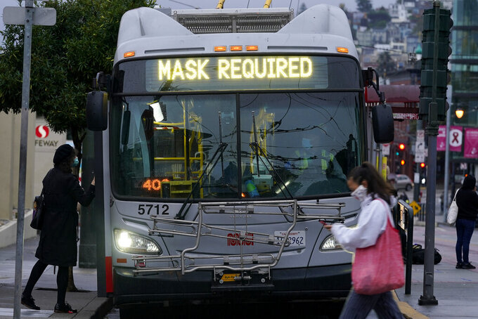 FILE - In this Tuesday, Nov. 17, 2020 file photo, a sign on a Muni bus in San Francisco advises that passengers are required to wear masks, during the coronavirus pandemic. (AP Photo/Jeff Chiu, File)