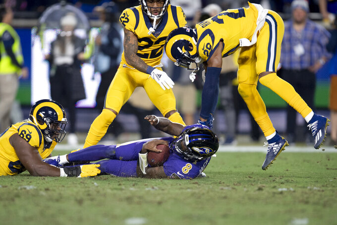 Baltimore Ravens quarterback Lamar Jackson, middle, is tackled by Los Angeles Rams defensive tackle Sebastian Joseph-Day, left, and cornerback Jalen Ramsey during the first half of an NFL football game Monday, Nov. 25, 2019, in Los Angeles. (AP Photo/Kyusung Gong)