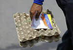 A Venezuelan man carrying a pack of eggs also clutches a flyer, given to him by Venezuelan politicians in exile, inviting people to come out to the streets on Feb. 23 to support a planned aid delivery to Venezuela, in La Parada, on the border with Venezuela, Colombia, Sunday, Feb. 17, 2019. As part of U.S. humanitarian aid to Venezuela, Sen. Marco Rubio, R-Fla, is visiting the area where the medical supplies, medicine and food aid is stored before it it expected to be taken across the border on Feb. 23. (AP Photo/Fernando Vergara)