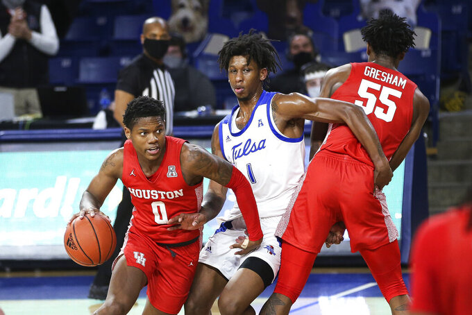 Houston's Marcus Sasser drives to the basket as Tulsa's Brandon Rachal fights around a screen set by Houston's Brison Gresham during the second half of an NCAA college basketball game in Tulsa, Okla., Tuesday, Dec. 29, 2020. Tulsa won 65-64. (AP Photo/Dave Crenshaw)