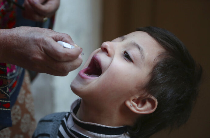 A healthcare worker administers a polio vaccine to a child in Peshawar, Pakistan, Monday, Jan. 11, 2021. Despite a steady rise in coronavirus cases, Pakistan on Monday launched a five-day vaccination campaign against polio amid tight security, hoping to eradicate the crippling children's disease this year. (AP Photo/Muhammad Sajjad)
