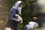 Migrant woman holds a cat as she stays an area between the borders of Belarus and Poland in the village of Usnarz Gorny, Poland, on Friday Aug. 20, 2021. A refugee rights group in Poland said Friday that 32 people who fled Afghanistan have been trapped for 12 days in an area between the Polish and Belarusian borders, caught up in a standoff between the two countries. (AP Photo/Michal Kosc)