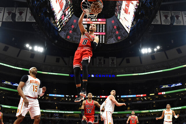 Chicago Bulls guard Zach LaVine (8) dunks the ball as Atlanta Hawks guard Vince Carter (15) stands nearby during the first half of an NBA basketball game, Wednesday, Dec. 11, 2019, in Chicago. (AP Photo/David Banks)