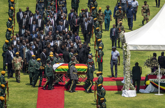 The casket of former president Robert Mugabe, covered by the national flag and followed by family and dignitaries, arrives for a state funeral at the National Sports Stadium in the capital Harare, Zimbabwe Saturday, Sept. 14, 2019. African heads of state and envoys are gathering to attend a state funeral for Mugabe, whose burial has been delayed for at least a month until a special mausoleum can be built for his remains. (AP Photo/Ben Curtis)