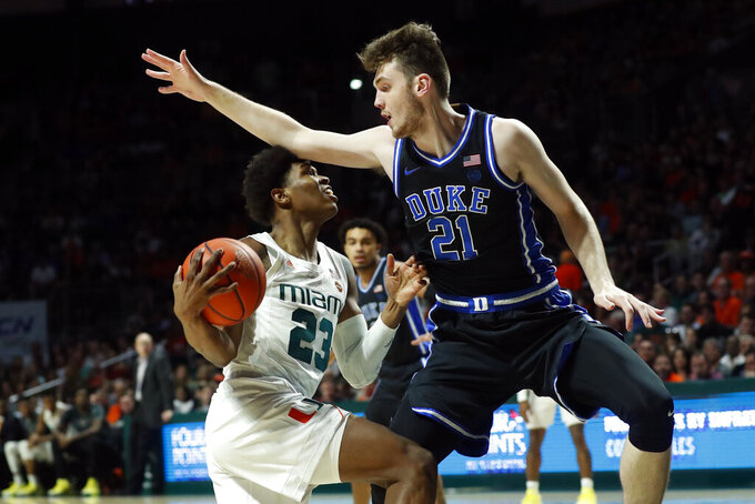 Miami guard Kameron McGusty, left, drives to the basket against Duke forward Matthew Hurt (21) during the first half of an NCAA college basketball game, Saturday, Jan. 4, 2020, in Coral Gables, Fla. (AP Photo/Wilfredo Lee)