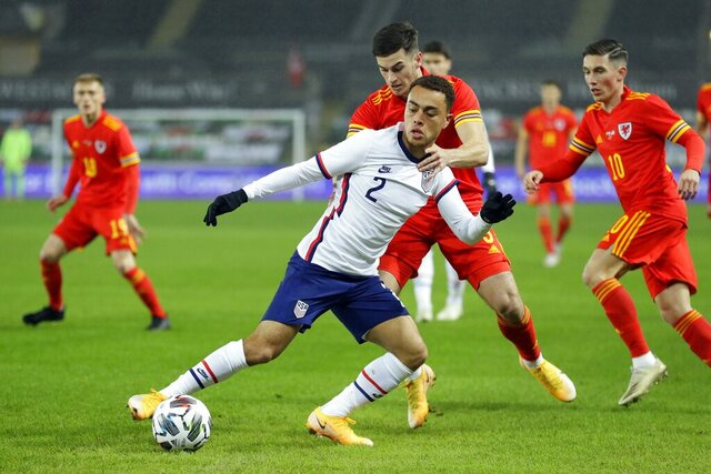 United States' Sergino Dest, foreground, controls the ball as Wales' Tom Lawrence tries to top him during the international friendly soccer match between Wales and USA at Liberty stadium in Swansea, Wales, Thursday, Nov. 12, 2020. (AP Photo/Kirsty Wigglesworth)