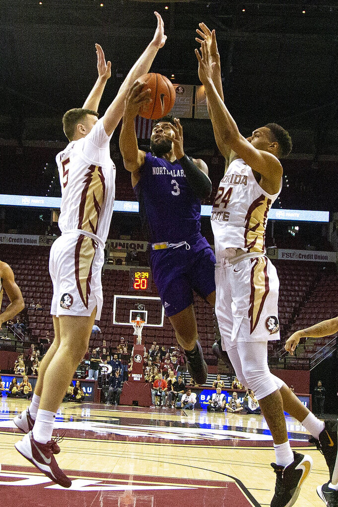 North Alabama guard Jamari Blackmon, center, tries to shoot between Florida State center Balsa Koprivica, left, and Florida State guard Devin Vassell, right, in the first half of an NCAA college basketball game in Tallahassee, Fla., Saturday, Dec. 28, 2019. (AP Photo/Mark Wallheiser)