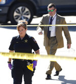Montgomery County Sheriff's Crime Scene Investigator Celestina Rossi, foreground, helps work the scene ahead of Major Crimes Division Chief Rob Freyer after two men attempted to rob a Brinks security armored truck at a bank Tuesday, Nov. 19, 2019, in Willis, Texas. Authorities say a guard fatally shot a person suspected of trying to rob the armored truck at a bank north of Houston and another suspect remains on the run. (Jason Fochtman/Houston Chronicle via AP)