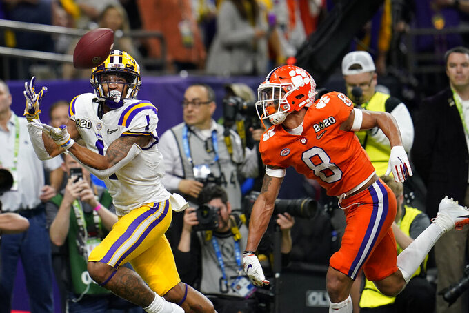 FILE - In this Jan. 13, 2020, file photo, LSU wide receiver Ja'Marr Chase catches a touchdown pass in front of Clemson cornerback A.J. Terrell during the first half of a NCAA College Football Playoff national championship game in New Orleans. All-America wide receiver Chase, cornerback Kary Vincent Jr. and defensive end Neil Farrell Jr. have announced they won't be playing this season. (AP Photo/David J. Phillip, File)