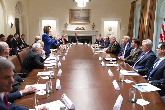 In this photo released by the White House, President Donald Trump, center right, meets with House Speaker Nancy Pelosi, standing left, Congressional leadership and others, Wednesday, Oct. 16, 2019, in the Cabinet Room of the White House in Washington. (Official White House Photo by Shealah Craighead via AP)
