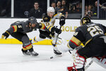 Boston Bruins center Charlie Coyle (13) shoots around Vegas Golden Knights defenseman Deryk Engelland (5) during the third period of an NHL hockey game Tuesday, Oct. 8, 2019, in Las Vegas. (AP Photo/John Locher)
