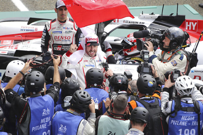 Spanish driver Fernando Alonso jubilates as his team win the 87th 24-hour Le Mans endurance race, in Le Mans, western France, Sunday, June 16, 2019. (AP Photo/David Vincent)
