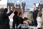 Audience members comfort each other during remembrance ceremony commentating the 20th anniversary of the attack on USS Cole at Naval Station Norfolk in Norfolk, Va. on Monday, Oct. 12, 2020. (Jonathon Gruenke/The Virginian-Pilot via AP)