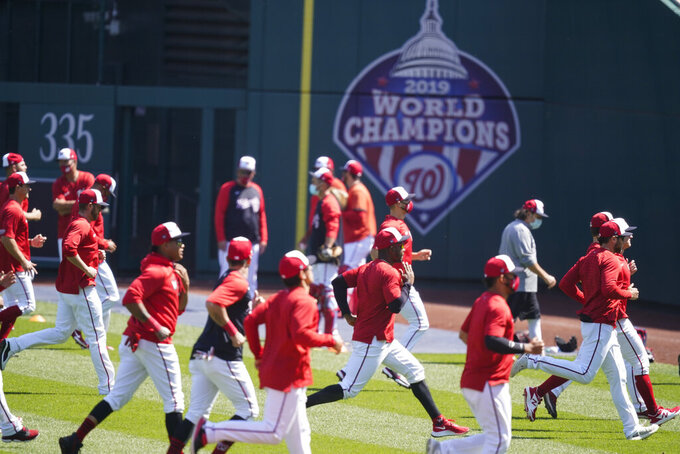 Washington Nationals warm up during a baseball workout at Nationals Park, Monday, April 5, 2021, in Washington. The Nationals are scheduled to play the Braves on Tuesday. (AP Photo/Alex Brandon)