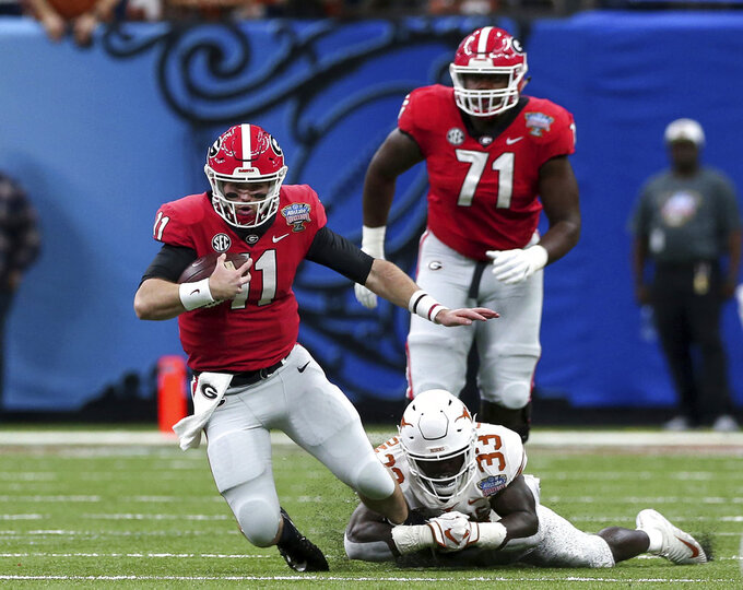 Texas linebacker Gary Johnson (33) tries to stop Georgia quarterback Jake Fromm (11) during the first half of the Sugar Bowl NCAA college football game in New Orleans, Tuesday, Jan. 1, 2019. (AP Photo/Rusty Costanza)