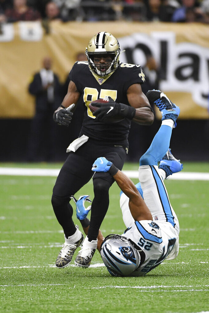 New Orleans Saints tight end Jared Cook (87) runs the ball as Carolina Panthers strong safety Eric Reid (25) attempts to tackle, during the first half at an NFL football game, Sunday, Nov. 24, 2019, in New Orleans. (AP Photo/Bill Feig)