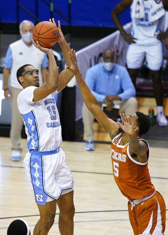 North Carolina forward Garrison Brooks (15) takes aim for the basket over Texas forward Royce Hamm Jr. (5) in the second half of an NCAA college basketball game for the championship of the Maui Invitational, Wednesday, Dec. 2, 2020, in Asheville, N.C. Texas won 69-67. (AP Photo/Kathy Kmonicek)