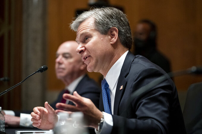Secretary of Homeland Security Alejandro Mayorkas, left, and FBI Director Christopher Wray, testify before a Senate Homeland Security and Governmental Affairs Committee hearing to discuss security threats 20 years after the 9/11 terrorist attacks, Tuesday, Sept. 21, 2021 on Capitol Hill in Washington.  (Greg Nash/Pool via AP)