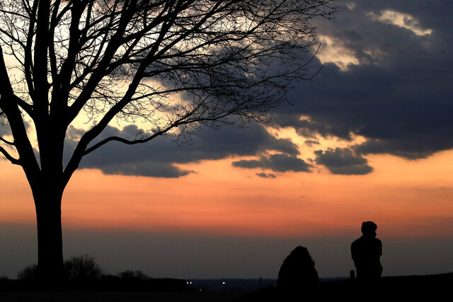 People watch the sunset from a park Tuesday, March 31, 2020, in Kansas City, Mo., as a stay-at-home order continues because of the coronavirus outbreak. (AP Photo/Charlie Riedel)