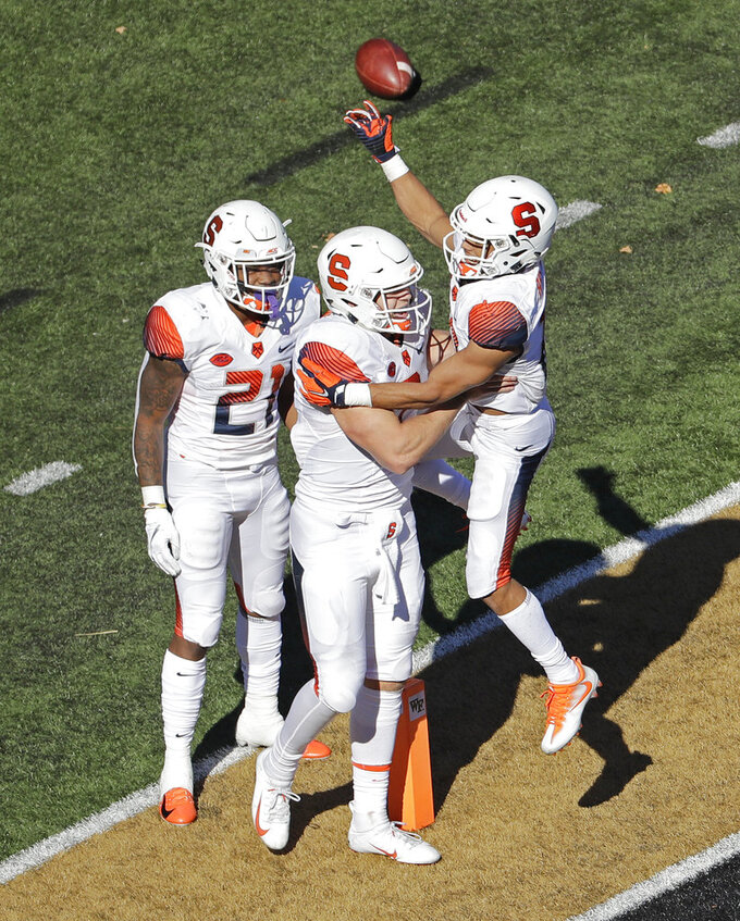 Syracuse's Eric Dungey, center, celebrates his touchdown against Wake Forest with teammates Moe Neal, left, Sean Riley, in the second half of an NCAA college football game in Charlotte, N.C., Saturday, Nov. 3, 2018. (AP Photo/Chuck Burton)