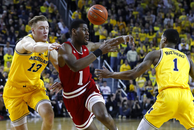 Michigan guard Charles Matthews, right, knocks the ball away from Indiana guard Aljami Durham, center, as Michigan's Ignas Brazdeikis (13) defends in the first half of an NCAA college basketball game in Ann Arbor, Mich., Sunday, Jan. 6, 2019. (AP Photo/Paul Sancya)