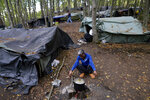 A migrant cooks on an open fire at a makeshift camp in a forest outside Velika Kladusa, Bosnia, Friday, Sept. 25, 2020. (AP Photo/Kemal Softic)