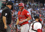 Los Angeles Angels' Mike Trout reacts to home plate umpire Brian O'Nora, who called Trout out on strikes during the first inning of the team's  baseball game against the Boston Red Sox at Fenway Park, Thursday, Aug. 8, 2019, in Boston. Red Sox catcher Sandy Leon is at right. (AP Photo/Elise Amendola)