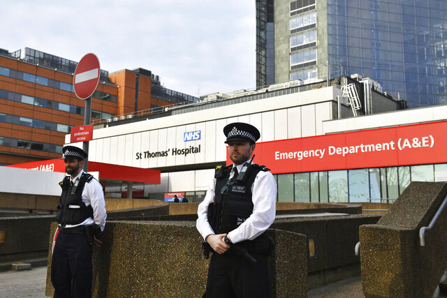 Police officers stand outside St Thomas' Hospital in the background in central London, where Prime Minister Boris Johnson remains in intensive care as his coronavirus symptoms persist, Wednesday April 8, 2020. Johnson has spent his second night in hospital intensive care.  The highly contagious COVID-19 coronavirus has impacted on nations around the globe, many imposing self isolation and exercising social distancing when people move from their homes. (Dominic Lipinski/PA via AP)