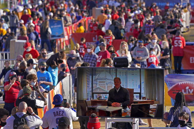 People watch NFL commissioner Roger Goodell on a screen at the NFL Experience Thursday, Feb. 4, 2021, in Tampa, Fla. The city is hosting Sunday's Super Bowl football game between the Tampa Bay Buccaneers and the Kansas City Chiefs. (AP Photo/Charlie Riedel)